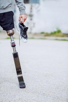 スニーカーを手に屋外で立っている白人の障害を持つスポーティな男の写真を切り取ります。