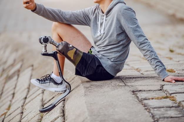잘 생긴 백인 장애인 운동가 스포츠웨어와 부두에 앉아 셀카를 찍는 인공 다리의 사진을 잘라냅니다.