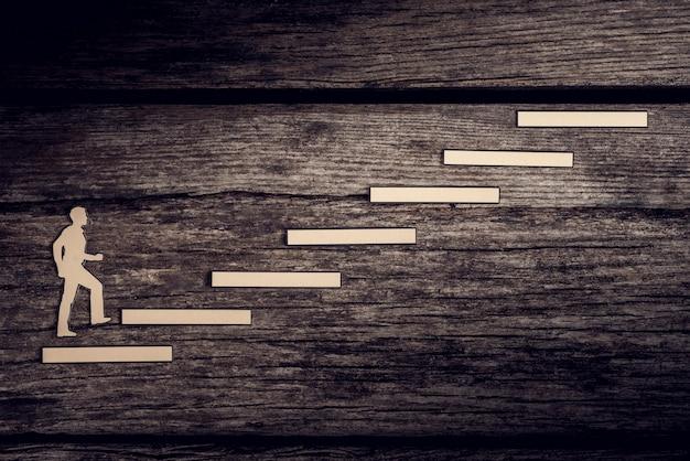 Вырезы из бумаги человек поднимается по ступенькам