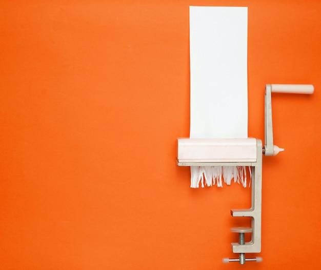 オレンジ色の背景にパスタを切るための手動機で紙を切る