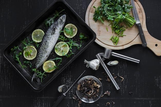 魚の近くのパセリとスパイスをカット