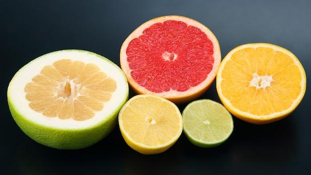暗闇の中でさまざまな柑橘系の果物の断片をカットします