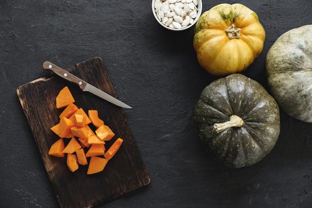 Нарезать кусочки сырой тыквы на деревянной разделочной доске на столе
