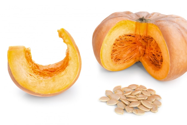Cut pieces of pumpkin soup and slices and seeds. on a white wall.