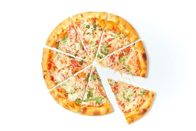Разрезать пиццу на кусочки на изолированном белом