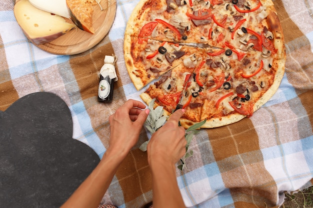 Cut pizza at picnic in sunday park.