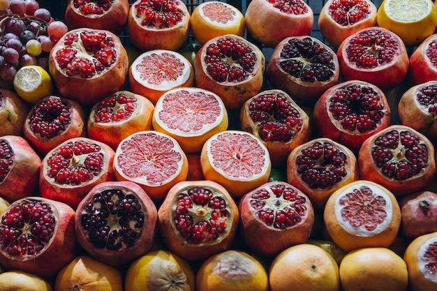 ザクロと柑橘類のカットがフレッシュジュースを作るために展示されています