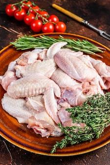Нарезать сырые куриные крылышки в деревенской тарелке с тимьяном и розмарином.