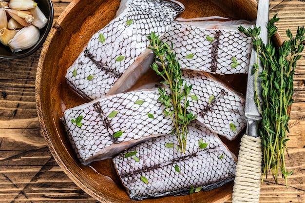 Нарезать сырую белую рыбу гренадер макрурус без головы в деревянной тарелке.