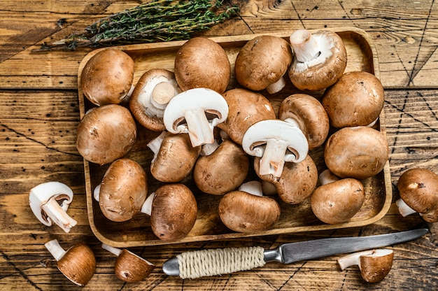 Нарезать сырые грибы коричневые шампиньоны. деревянный фон. вид сверху.