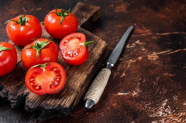 Нарезать красные помидоры черри на деревянной разделочной доске. темный фон. вид сверху. скопируйте пространство.