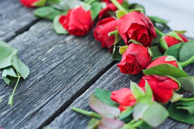 木製の背景に赤い枯れたバラをカットします。
