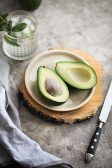 Cut ripe avocado on a plate on a wooden plank next to a knife and a napkin on a gray.