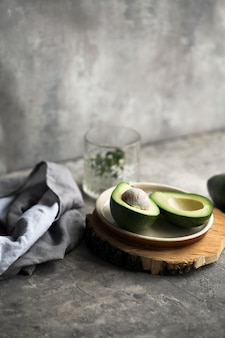 Cut ripe avocado on a plate on a wooden plank next to a napkin and glass on a gray.