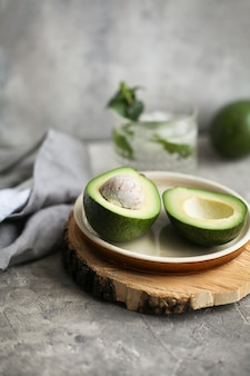 Cut ripe avocado on a plate on a wooden plank next to a napkin on a gray.