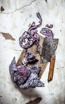 素朴な背景に手斧で熟したキャベツをカット