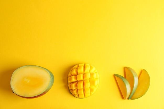 Вырезать спелые манго и место для текста на цветном фоне, вид сверху