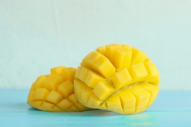 Cut ripe mangoes on color table
