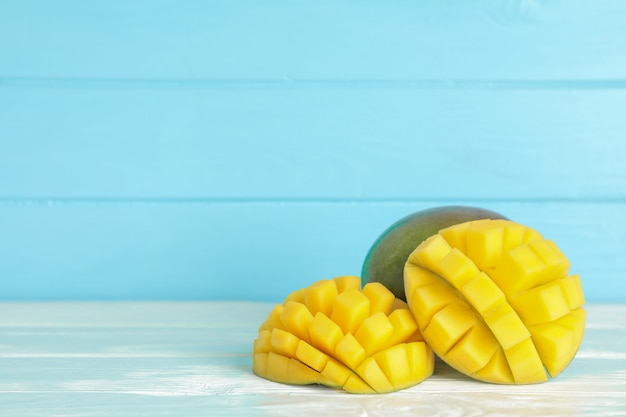 Cut ripe mangoes on white table