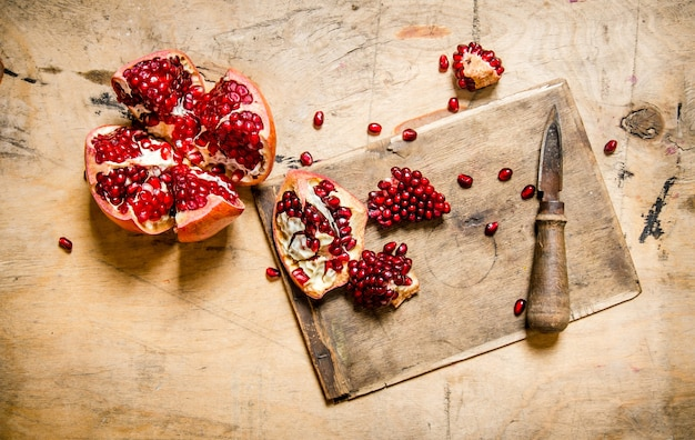Cut ripe pomegranate on the old board with a knife on a wooden surface