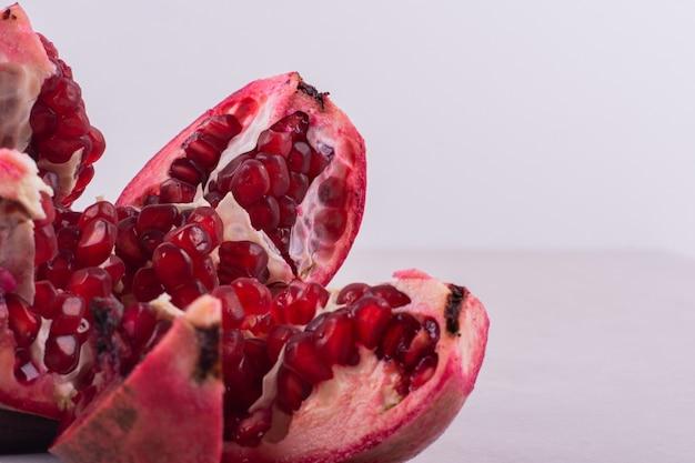 Cut ripe pomegranates on white wall.