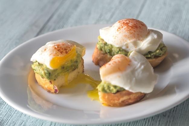 Нарезанный бутерброд с гуакамоле и яйцом-пашот
