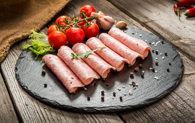 Cut sausage from ham on a wooden background
