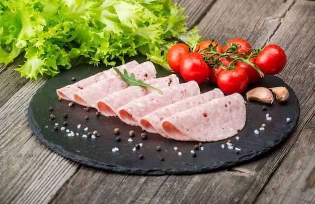 Cut sausage from ham on a wooden surface