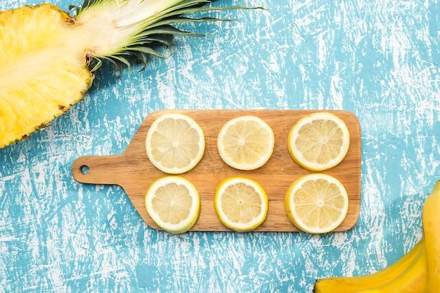 Нарезать ломтиками лимона на деревянной доске