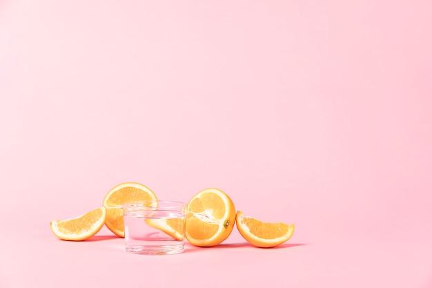 ピンクの背景にオレンジ色の果物のスライスをカット