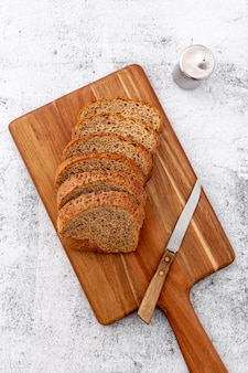 Cut slices of wholemeal bread on wooden board