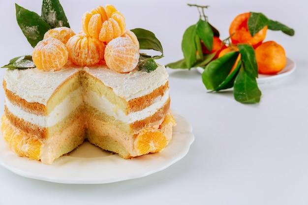 マンダリンクリームと新鮮なクレメンタインでスポンジケーキを切る