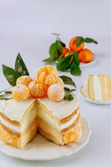 Cut sponge cake with mandarin cream and fresh clementines.