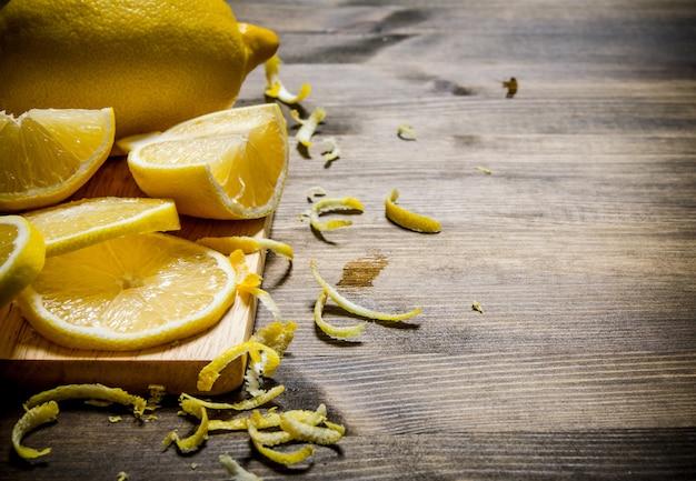 Цедру лимона порезать на доске. на деревянном столе. свободное место для текста.
