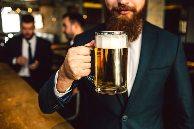 Cut view of bearded man in suit hold beer mug. other two office workers sit behind.