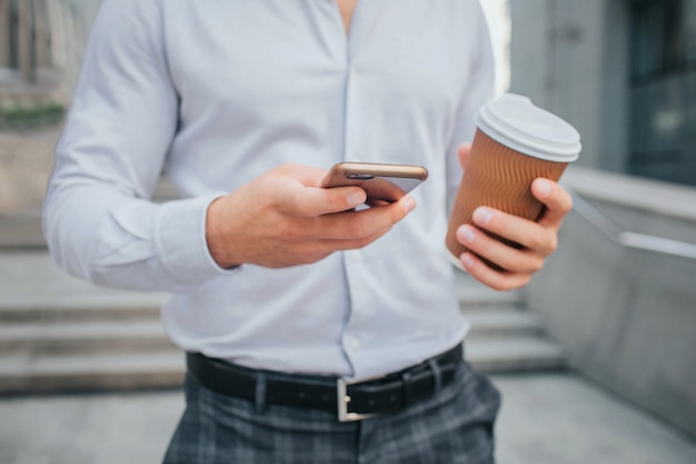 Cut view of body of young businessman stands and holds cup of coffee and phone.