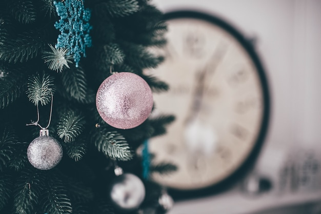Cut view and close up of piece of green christmas tree with white and pink round toys on it hanging. clock or watches behind on blurred background.