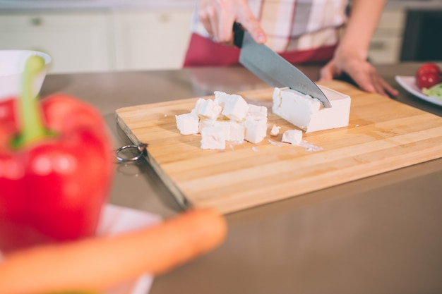 Cut view of female's hands cutting white cheese into pieces on desk.