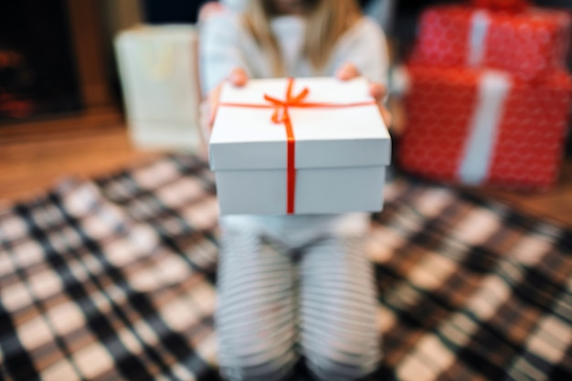 Cut view of girl sitting on knees and holding white box with present. there is red ribbon on it.