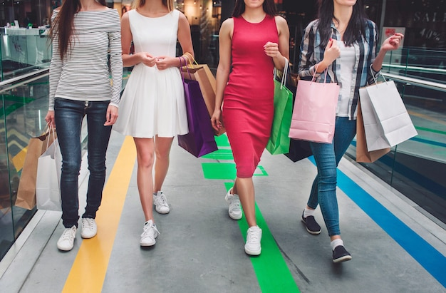 Cut view of girls walking together in a big store. they wear different clothes and have different colorful bags in their hands. young women are on shopping.