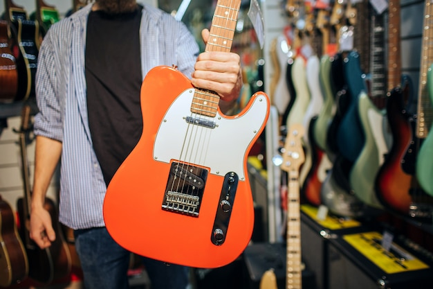 Cut view of man in guitar shop holding electric instrument in hand. he show it to camera. man is alone in room.