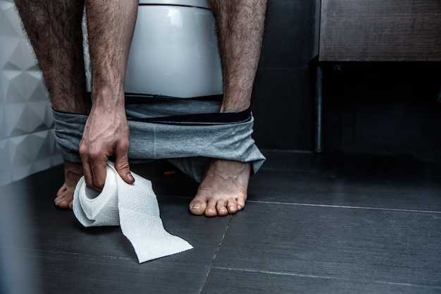 Cut view. man sit on toilet and reach paper. legs are thin and pale