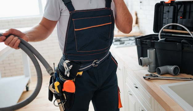 Cut view of man standing in kitchen and holding hose. he wear working uniform. tools on belt. guy stand at sink.