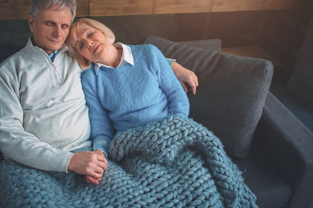 Cut view of married couple laying together on couch and holding