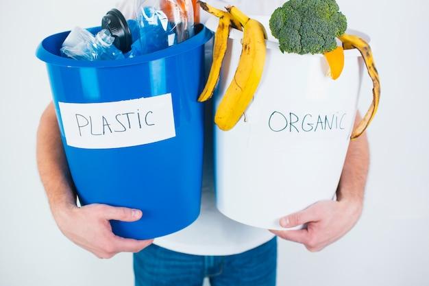 Отрежьте взгляд парня держа отделенные ведра с органическими и пластичными отходами. ответственное использование и утилизация. безотходный образ жизни.