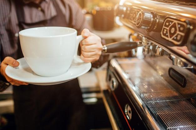 거대한 흰색 커피 컵을 손에 들고 있는 바리스타의 모습을 잘랐습니다. 그는 커피 머신에서 부엌에 서 있다