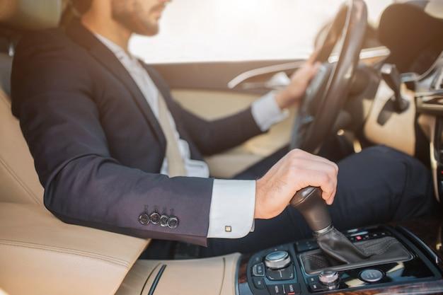 수염 난된 젊은이 차에 앉아서 운전의보기를 잘라. 그는 한 손은 핸들에, 다른 손은 핸드 브레이크에 넣습니다. 남자는 집중된다.
