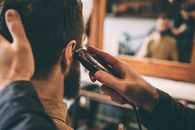 Вырезать вид парня стричь волосы клиента с помощью электрической бритвы возле правого уха. он держит голову и делает это очень точно.