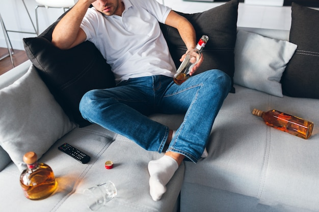 開いたボトルの中でウィスキーでソファーに座っている男のビューをカットします。頭痛や二日酔いに苦しんでいます。問題とストレス。絶望的な男はアルコールで悩みます。