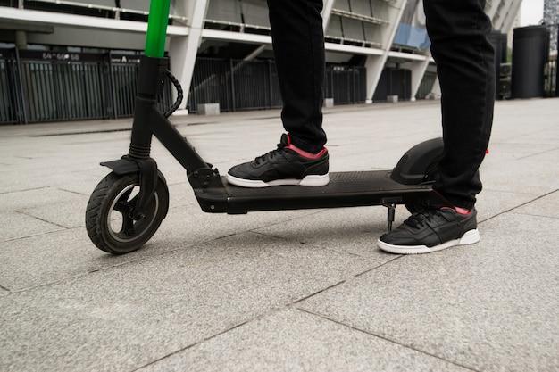 E-スクーターの上に立っている男性の足のカットビュー。大都市をドライブするスマートな方法。黒のスタイリッシュなスニーカー。男はスマホアプリで電動スクーターを借りた。エコ習慣。